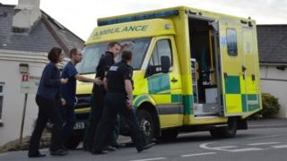 Police officer being helped to an ambulance
