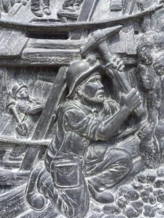 Stone carving of miner statue