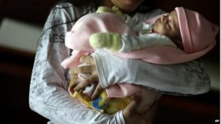 A 13-year-old girl holds her one-month old baby at a shelter for troubled children in Ciudad del Este, Paraguay, on Thursday, May 14, 2015.