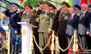 Ihar Shunievich salutes alongside other officials at the parade in Minsk