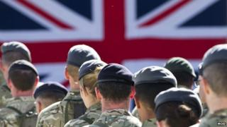 Male and female members of the armed forces gathered together for a remembrance service.