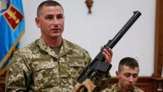 A Ukrainian soldier shows a weapon allegedly belonging to Russian servicemen captured by Ukrainian forces, during a briefing for media in General Staff of Ukrainian army in Kiev, Ukraine, 18 May 2015.