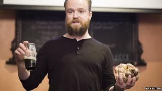 picture of scientist holding a brain and a pint