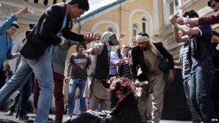 Afghans stage a re-enactment of the killing by a mob of an Afghan woman during a protest demanding her killers be brought to justice, in Kabul, Afghanistan, 27 April 2015