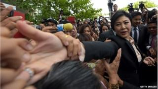 Yingluck Shinawatra shakes hands with her supporters outside the Supreme Court in Bangkok