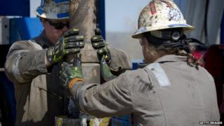 Workers change pipes at Consol Energy Horizontal Gas Drilling Rig exploring the Marcellus Shale outside the town of Waynesburg, Pennsylvania