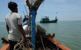 "A local fishermen (L), one of many who earlier in the day helped rescue migrant Rohingya from Myanmar and Bangladesh, looks at their abandoned ship off the coast near the city of Geulumpang in Indonesia""s East Aceh district of Aceh province on May 20, 2015."