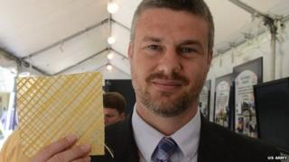 Nick Boone holds a square of ballistic wallpaper