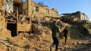 Reporter Yalda Hakim and camera operator walk through the rubble of a village in Nepal