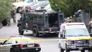 SWAT teams and other police officers wait during the standoff