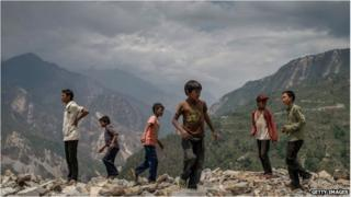 Children in the village of Marming play around on the ruins of their former school that was destroyed during the 25 April earthquake on 17 May.