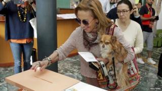 A woman holding a dog votes in Spain's local elections