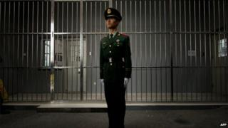 A paramilitary guard stands before the bars of a main gate to the No.1 Detention Center during a government guided tour in Beijing on 25 October 2012