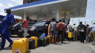 People queue with jerry cans to buy fuel at Mobil filling station in Lagos, on May 21
