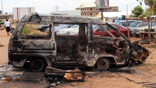 A woman walks near a minibus burnt by an angry mob in reaction to suicide bomb attacks on the Shallom Church of God during church service on Sunday in the Trikania neighbourhood in Kaduna, northern Nigeria political capital 18 June 2012