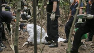 A forensics team digs at a grave found at Wang Burma hills at Wang Kelian, Perlis, Malaysia - 26 May 2015