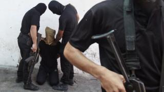 Hamas militants hold a Palestinian suspected of collaborating with Israel before he is executed in Gaza (August 2014)