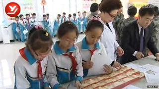 School children collect their account booklets at the bank