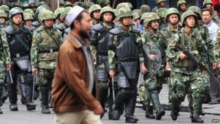 Armed Chinese soldiers march on patrol as a Uighur man crosses the street in Urumqi on July 15, 2009 in northwest China's Xinjiang province