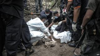 A Royal Malaysian Police forensic team handles exhumed human remains in a jungle at Bukit Wang Burma in the Malaysian northern state of Perlis, which borders Thailand, on May 26, 2015.