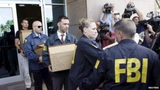 FBI investigators removing boxes from a building belonging to football authorities