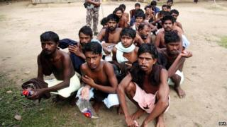 Rohingya Muslims from Bangladesh rescued by the Myanmar navy sit together at a temporary refugee camp in the village of Aletankyaw in Myanmar, 23 May 2015