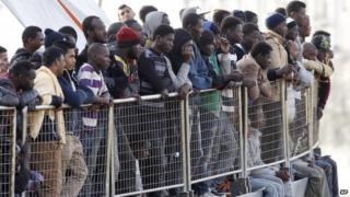 Migrants wait to disembark from a coastguard vessel at Messina harbour, Sicily, 6 May 2015