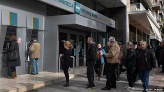 People wait to use an ATM in Greece