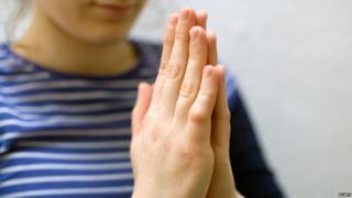 "Woman makes ""namaste"" gesture of courtesy"