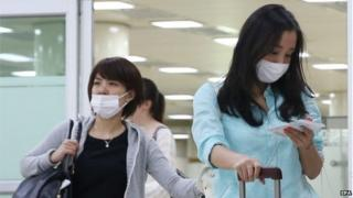 Two Japanese tourists wearing facial masks arrive at Gimpo airport, western Seoul, South Korea, 29 May 2015, as South Korea confirmed two additional cases of the Middle East Respiratory Syndrome (MERS), raising the number of patients diagnosed with the virus to nine.
