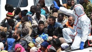 An Italian Coast Guard ship carrying migrants arrives at Pozzallo's harbour near Ragusa, Sicily, Italy, Tuesday, May 19, 2014.