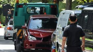 A damaged red car with a bullet hole in its windscreen is being towed away near the Shangri-La hotel in Singapore on 31 May 2015