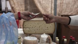 Consumer buys cheese at Athens market (30 May)