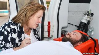 Casey Coombs lying on a stretcher upon his arrival in Oman
