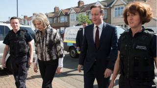 David Cameron and Theresa May with immigration enforcement officers following following an early morning raid on a home in London