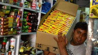 "An Indian shopkeeper carries a box of ""Maggi"" noodles through his shop in Delhi on June 3, 2015"
