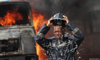 """A fireman cools off after petrol tankers, belonging to an oil service company, caught fire at Ogba neighbourhood in Nigeria""""s commercial capital Lagos February 2, 2010. No injuries were reported."""