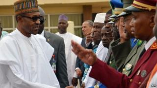 Nigerian President Muhammadu Buhari (left) shakes hands with officers in Niger