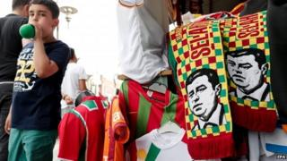 "A young boy walks near election-themed scarves showing a depiction of leader of the Peoples"" Democratic Party (HDP) Selahattin Demirtas, in Diyarbakir"
