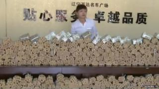 A member of staff standing behind a huge pile of coin rolls and notes