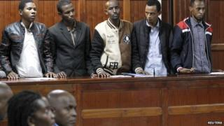 "Tanzanian national Rashid Charles Mberesero (L) stands inside the dock with Osman Abdi Dakane (2nd L), Sahal Diriye Hussein (C), Hassan Aden Hassan (2nd R), Mohamed Abdi Abikar (R) at the Milimani Law Courts in Kenya""s capital Nairobi, June 4, 2015"