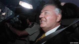Alan Bond leaves a Western Australian court in a police van in 1996