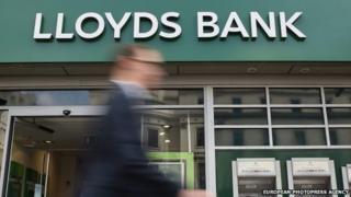 Pedestrians pass a Lloyds bank branch in central London