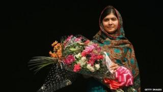 Malala Yousafzai holds a bouquet of flowers, given to her on behalf of the Pakistani Prime Minster