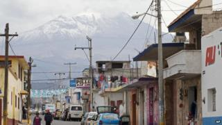 In this March 10, 2015 file photo, the Pico de Orizaba volcano rises above the town of Tlachichuca in Mexico's Puebla state.