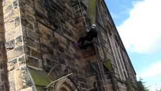 Bishop of Burnley abseiling down the church
