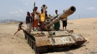 Fighters from the Southern Popular Resistance ride on a tank at the front line of fighting against Houthi fighters, on the outskirts of Yemen's southern port city of Aden (06 June 2015)