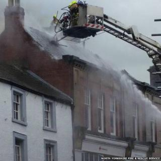 Firefighters on an aerial ladder putting out a fire in the roof of a shop building