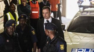Oscar Pistorius is escorted to a police van after his sentencing at the North Gauteng High Court in Pretoria on October 21st 2014