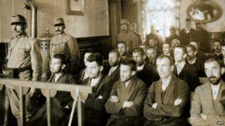An archive photo of Gavrilo Princip and his co-accused on trial in a courtroom, flanked by guards